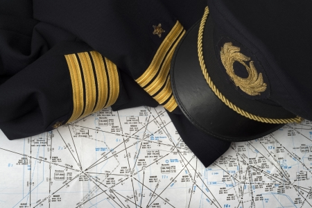 aeronautical: not worn captain uniform over an aeronautical navigation chart