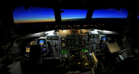 View of a plane cockpit in flight toward a sunset