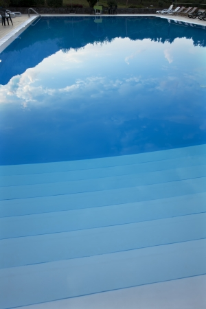 Mountains and clouds reflected in a pool at sunset Stock Photo