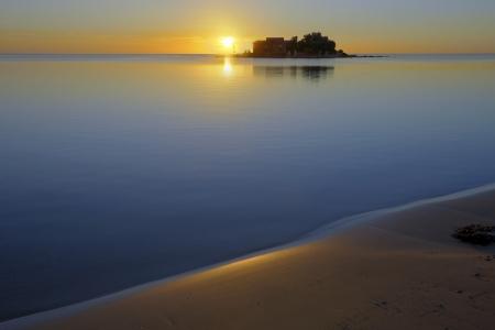 Sunrise on an empty beach and a calm sea Stock Photo