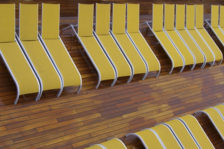 Rows of yellow deckchair without people on a wooden floor