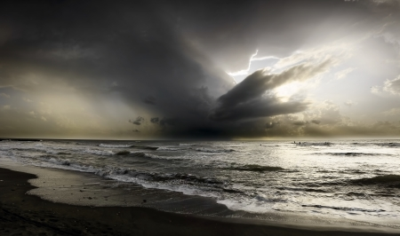 A storm on the sea just behind  many surfers Stock Photo