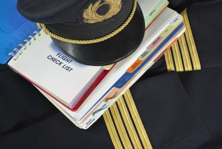 procedure: Captain uniform and aircraft check list for aircraft emergency procedure Stock Photo