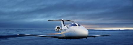 Executive plane flying at sunset Stock Photo