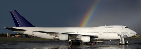 Aircraft parked with a rainbow behind photo