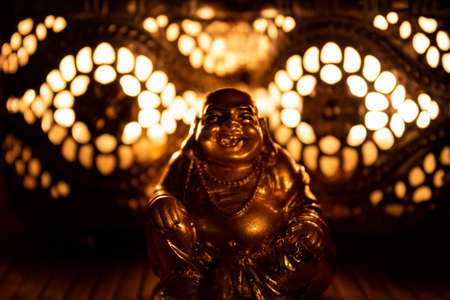 golden monk sculpture illuminated by candle light, close up. buddhism concept Stock Photo