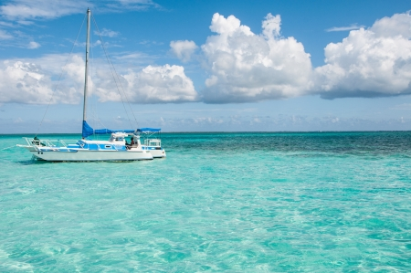 Boat in the middle of Caribbean sea surrounded by blue skye and clouds
