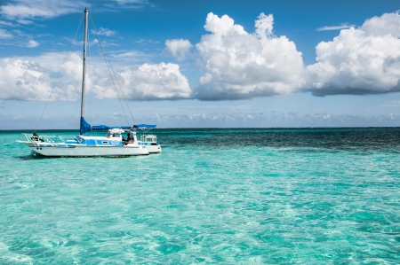 Boat in the middle of Caribbean sea surrounded by blue sky and clouds  Banque d'images