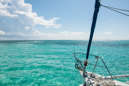 Boat in the middle of Caribbean sea surrounded by blue sky and clouds  版權商用圖片