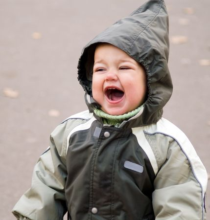 playful behaviour: Happy shouting baby in green autumn jumpers with hood