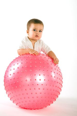 Thoughtful dark hired boy with pink fitness ball on white background photo