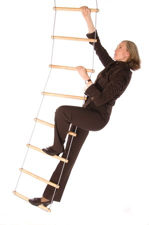 Young woman in brown suit climbering  the rope-ladder isolated on white Stock Photo