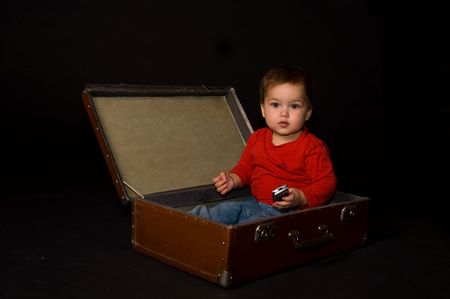 Surprised boy holding phone in luggage photo