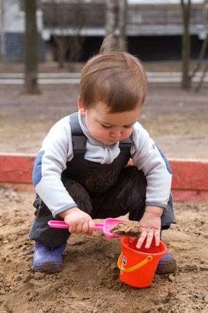 the sandbox: Child sitting in sandbox on cold spring day Stock Photo