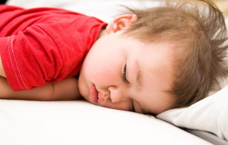 Boy in red dress sleeping on bed (napping)