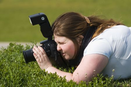 Woman-photographer with camer aiming at someting against green grqss photo