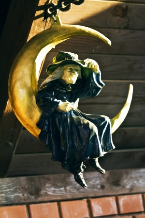 Figure of witch sitting on the crescent photo