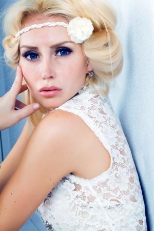 Portret van mooie jonge blonde vrouw op blauwe achtergrond