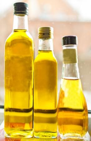 drie flessen met olijfolie staan bij het raam