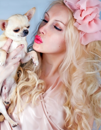 Beautiful blond woman kissing  tiny chihuahua in hands photo