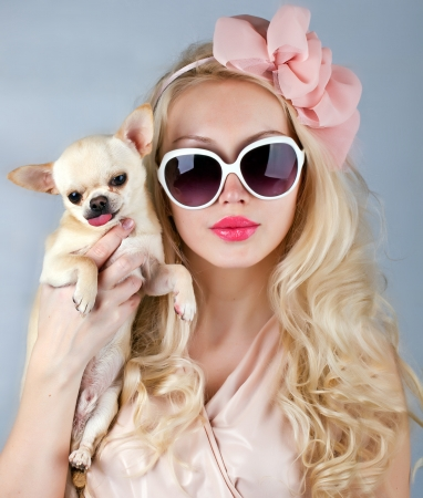 mooie glamour vrouw in zonnebril met kleine hond in handen
