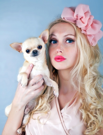 pupy: Beautiful blond woman in pink with cute small dog Stock Photo