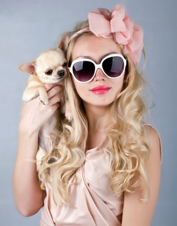 beautiful smiling  woman in sun glasses and small chihuahua in hands photo