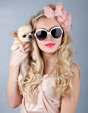 mooie lachende vrouw in zonnebril en kleine chihuahua in handen