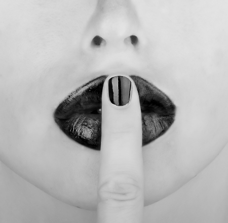 finger on lips black and white picture