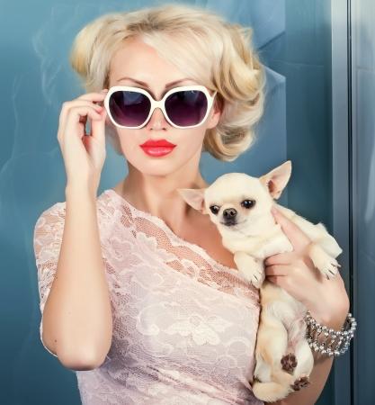 aantrekkelijke vrouw in een zonnebril met smal hond in de hand