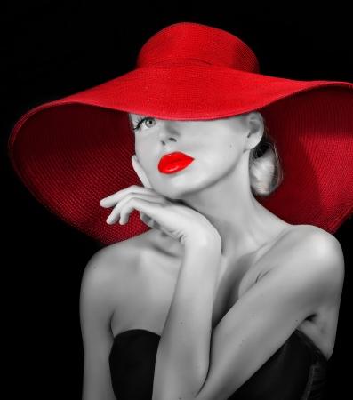 romantische vrouw in de rode hoed op zoek naar camera