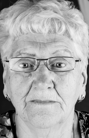face of an old woman in glasses black and white picture photo