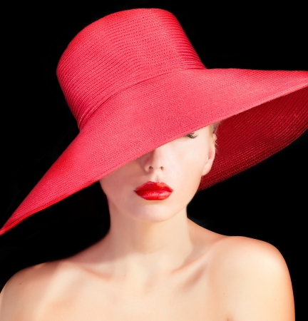 beautiful mysterious woman with red lips and in hat over black background