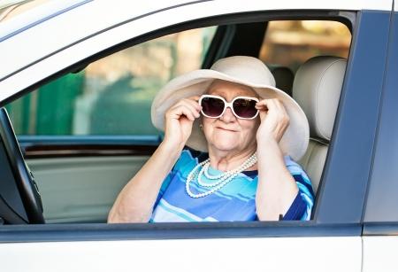 oude vrouw in een zonnebril in de auto zitten.