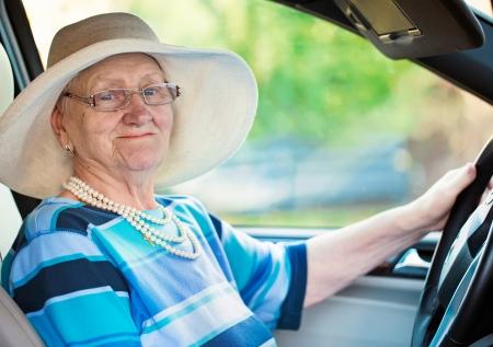 glimlachende oude vrouw in glazen rijden auto Stockfoto