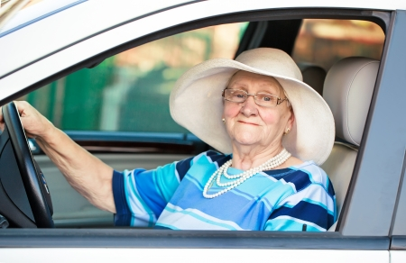 senior lady in glasses driving automobile Stock Photo