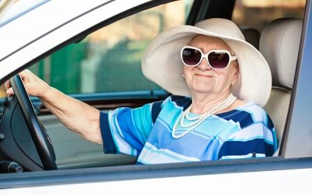 gelukkig senior vrouw in een zonnebril en hoed rijden auto. Stockfoto