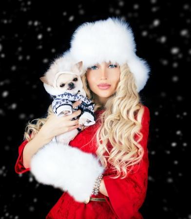 mooie vrouw met leuke chihuahua in handen in warme kleren en bontmuts Stockfoto