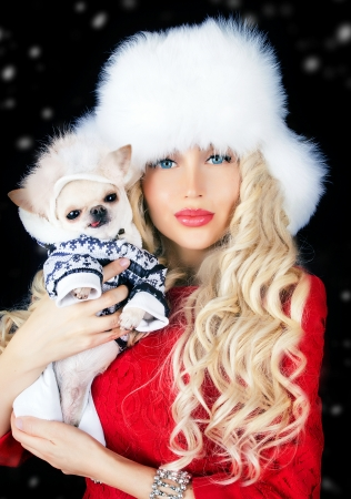 winter fashion: beautiful blonde woman with small dog in hands Stock Photo