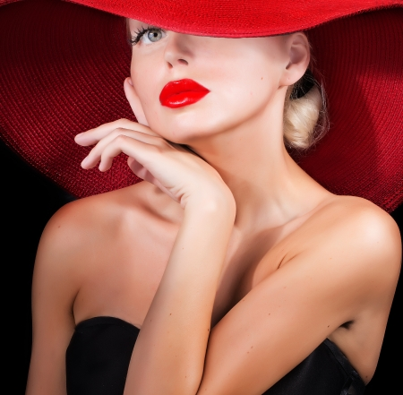 beautiful model  in red hat with red lips looking at camera photo