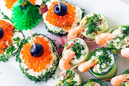 tasty snack with red caviar on french bread and shimps with cucumber and dressing photo