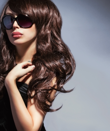 elegant woman in sunglasses with long wavy shiny hair photo