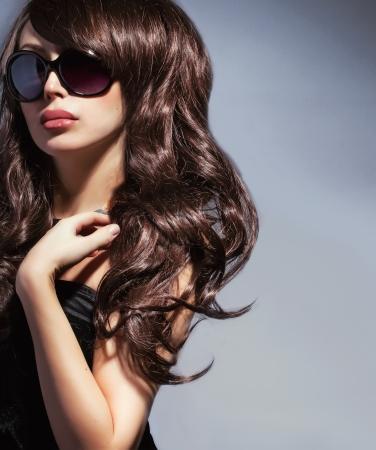 elegante vrouw in een zonnebril met lang golvend glanzend haar Stockfoto
