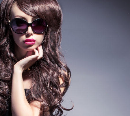 young brunette in sunglasses looking at camera photo