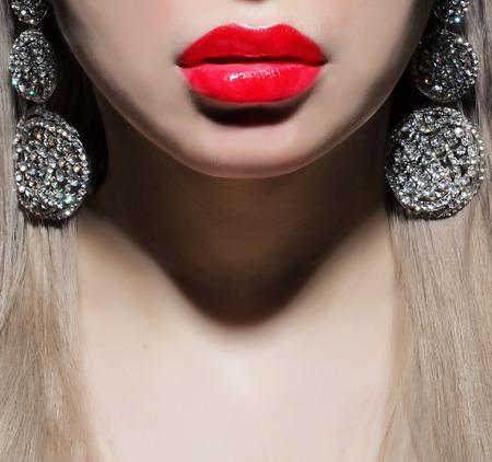 een deel van het gezicht met rode lippen en oorbellen