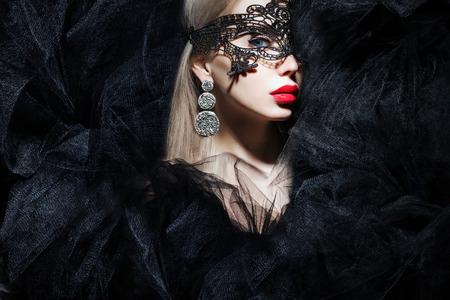 modelos negras: mujer mística en la máscara y los labios rojos mirando a la cámara Foto de archivo