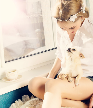 frienship: beautiful woman playing with small dog at window