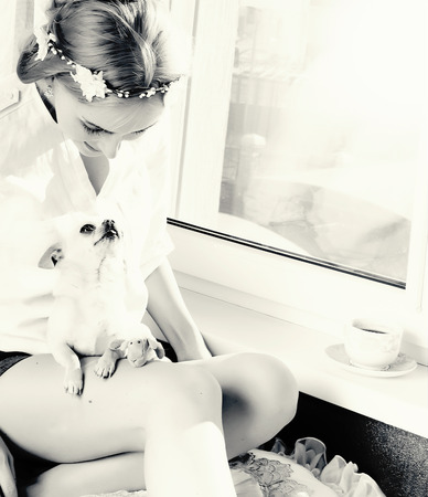 beautiful girl playing with small dog black and white picture