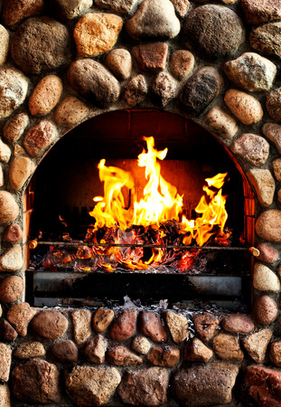 stone fireplace:  old brick stove with glowing fire . Stock Photo