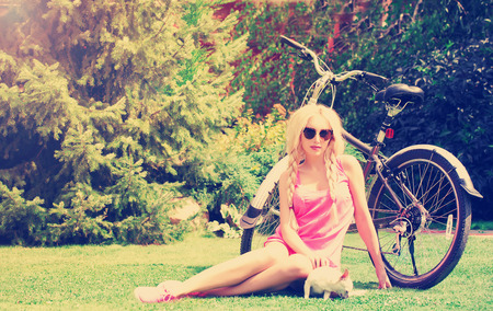 woman with small dog and bicycle in the park . photo